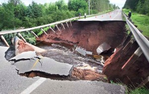 "The Lester River flows through a gash it created in Jean Duluth Road north of Duluth, Minn., Thursday morning, June 21, 2012. City, county and state officials spent Thursday assessing damage, while areas farther south continued to fight rising floodwaters. The town of Moose Lake was being described as ""an island."" (AP Photo/The News-Tribune, Bob King)"