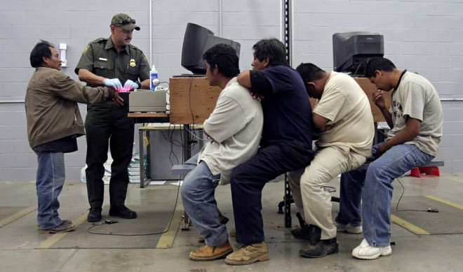 A man has his fingerprints scanned by a U.S. Border Patrol agent while others wait their turn. Reuters/Jeff Topping